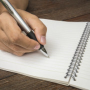 Male hand with pen writing on notebook