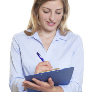 Blond businesswoman with clipboard writing note on an isolated white background for cut out