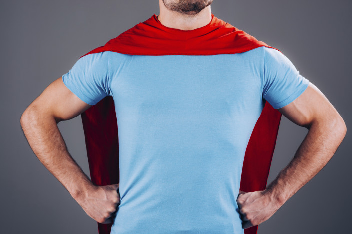 a guy wearing a blue shirt and a red super hero cape